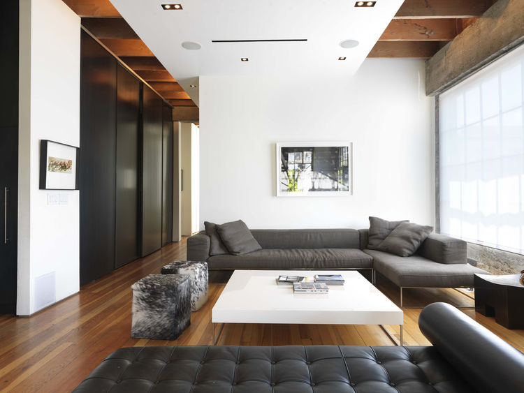 Open-plan living room with high ceilings and white walls