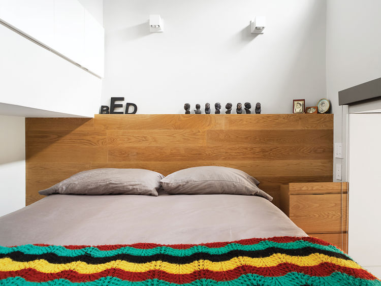Bed with colorful knit blanket and grey bedding