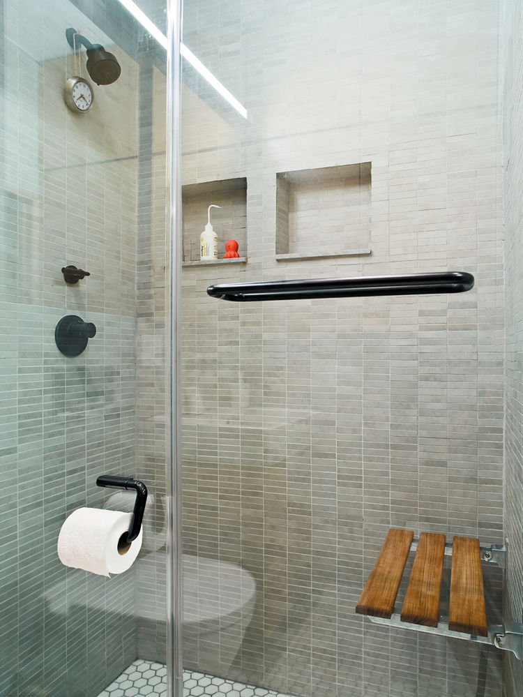 Modern shower with teak bench and tiled wall