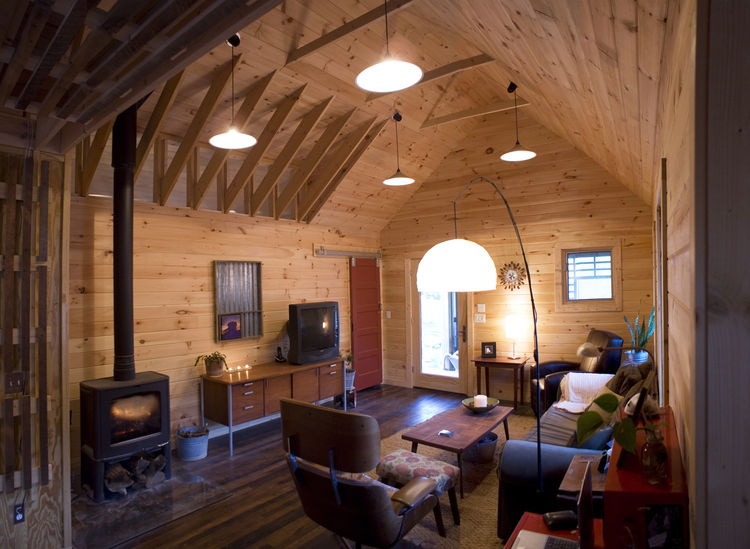 Inside the main living area, tongue-and-grooved white pine covers the walls and vaulted ceilings, and a red closet door, built of salvaged pine from the original house, slides open and closed on barn track hardware.