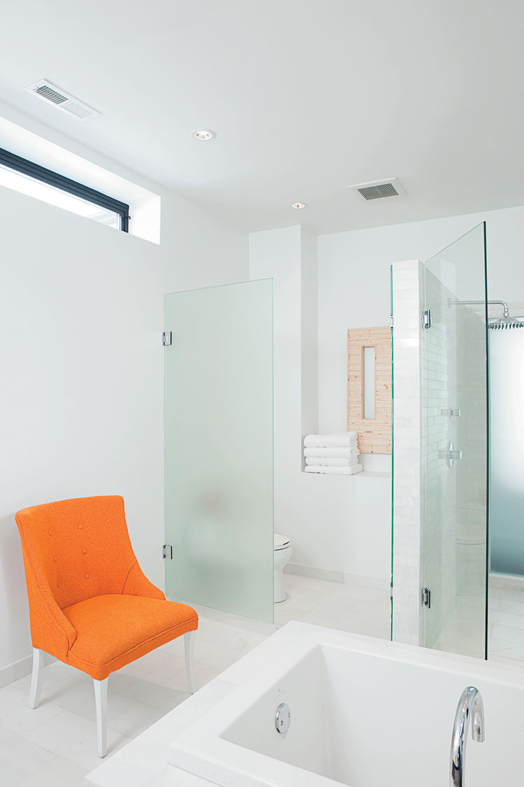 The master bathroom, with its frosted glass walls and chair (rescued from the trash pile and rehabbed), is large and elegant enough to serve as a gathering place for parties.