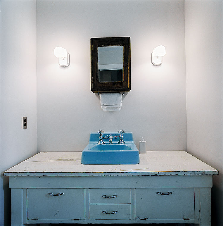 For the bathroom inside Blake Dollahite's formerly rundown Austin bungalow, he repurposed a beat-up white credenza that he'd had in storage for years by fitting it with a robin's-egg-blue sink from a Habitat for Humanity ReStore. With an aged mirror and s