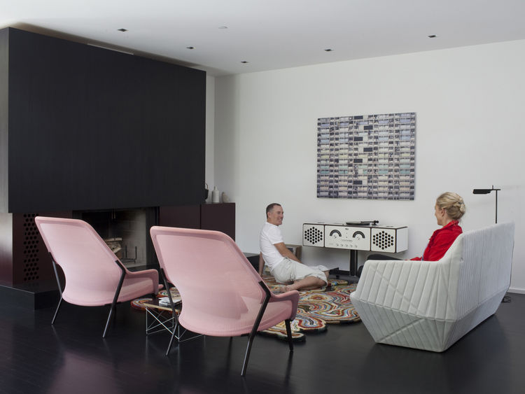 Modern living room with Ligne Roset sofa and pink Vitra chairs