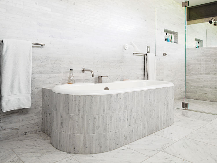 Master bathroom with walls and tub clad in Carrara marble