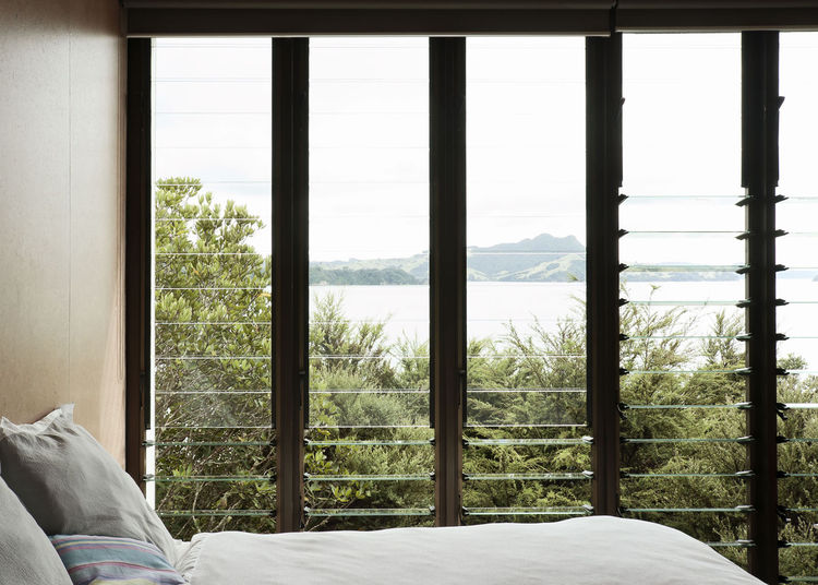 Modern bedroom with louvered windows and a view of Maramaratotara Bay