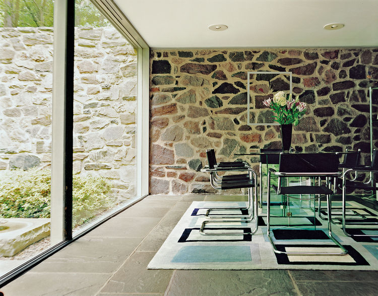 Three stark planes make the dining room a place of sun and shadow: a wall of rock, a floor of bluestone, and a sheer slice of glass. Further adding to the unity of the house, the tubular steel dining chairs were also designed by Breuer.