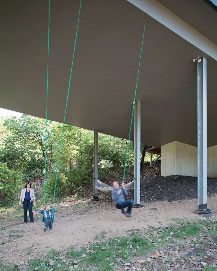 Julie, James, and Christian enjoy an unexpected bonus of living in a house on stilts—–a pair of swings suspended from the base of the structure. The family often goes for walks on the property, looking for wildlife and playing in the tepee they built in a