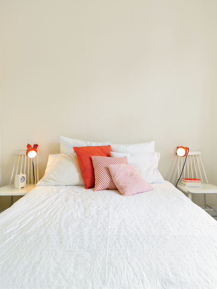 Bedroom with white bedding and mini orange lamps