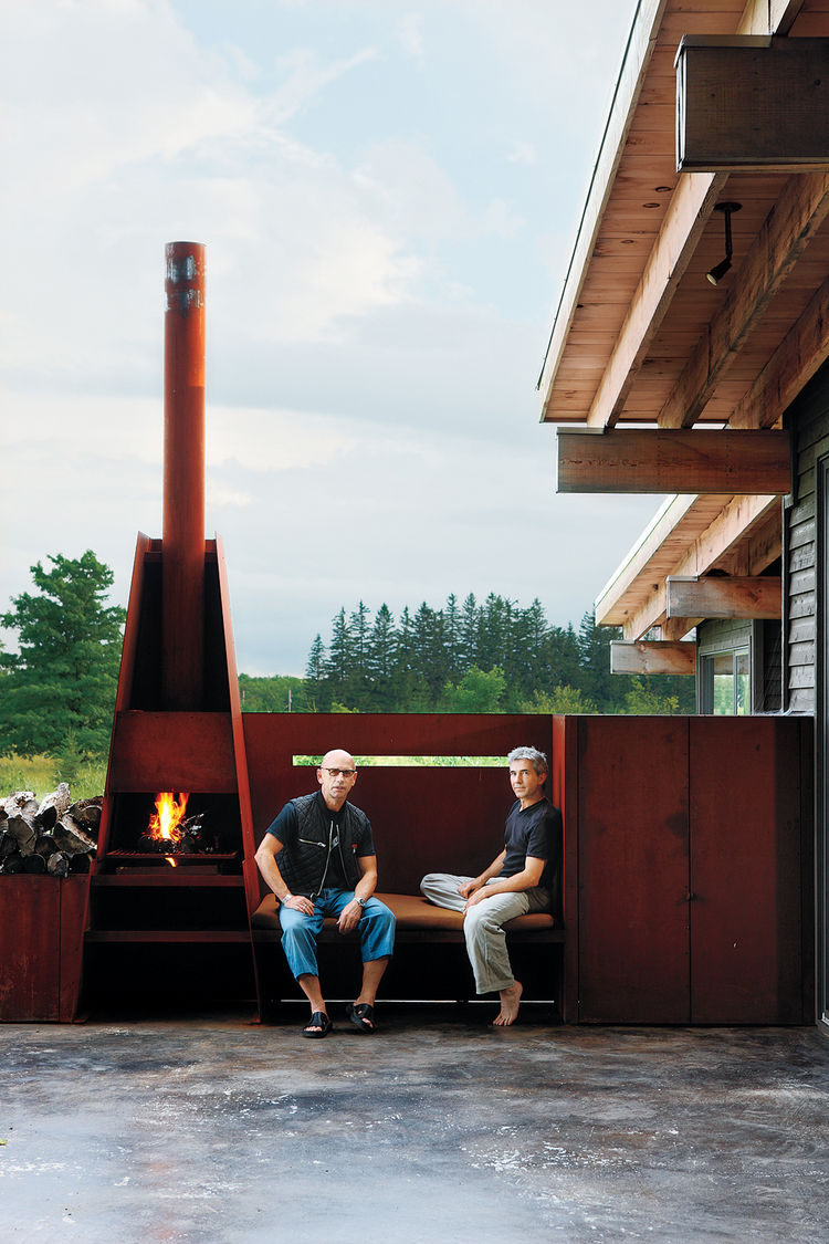 Metals broker S. J. Sherbanuk (left) and designer James Campbell sit by the outdoor fireplace, which adjoins the screened-in porch. The house was constructed of recycled metals, and is located in Town of the Blue Mountains, 90 minutes northwest of Toronto