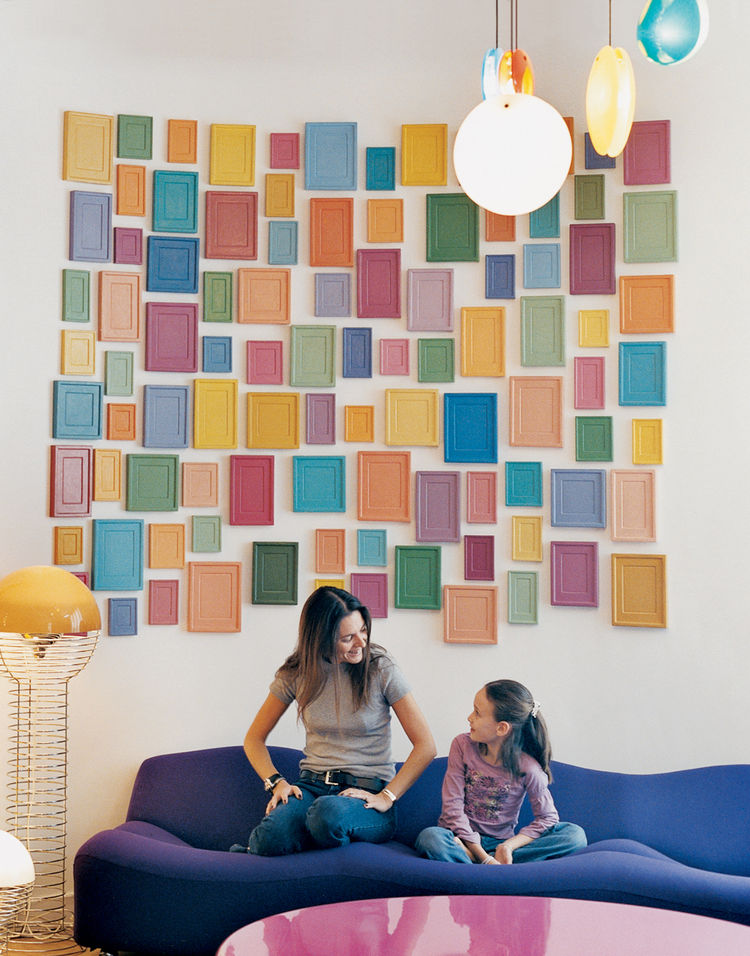 Clémence and daughter Clara, nine, relax on a purple Pierre Paulin 261 sofa below an installation by artist Alan McCollum. A small family of Verner Panton 1969 Wire lamps, featured in the inaugural Kreo exhibition, live to the left.
