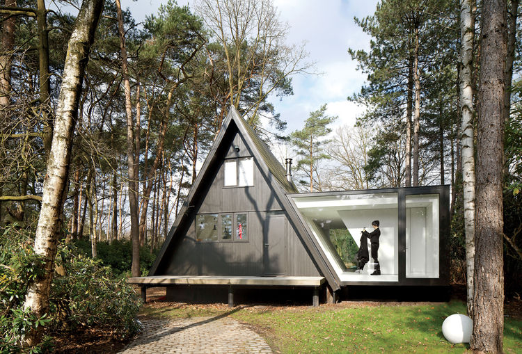Modern A-frame structure with glass extension in Belgium.