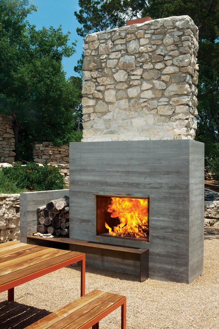 Modern outdoor fireplace area with wooden benches