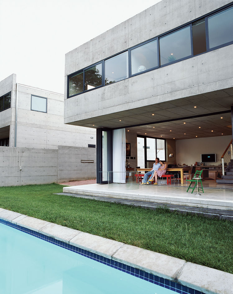 Gregory and Caryn Katz are dwarfed beneath the cantilevered concrete overhang, which houses the bedroom on the upper level. The stackable glass doors that run beneath allow the house to open completely to the yard and swimming pool, soften the severity of