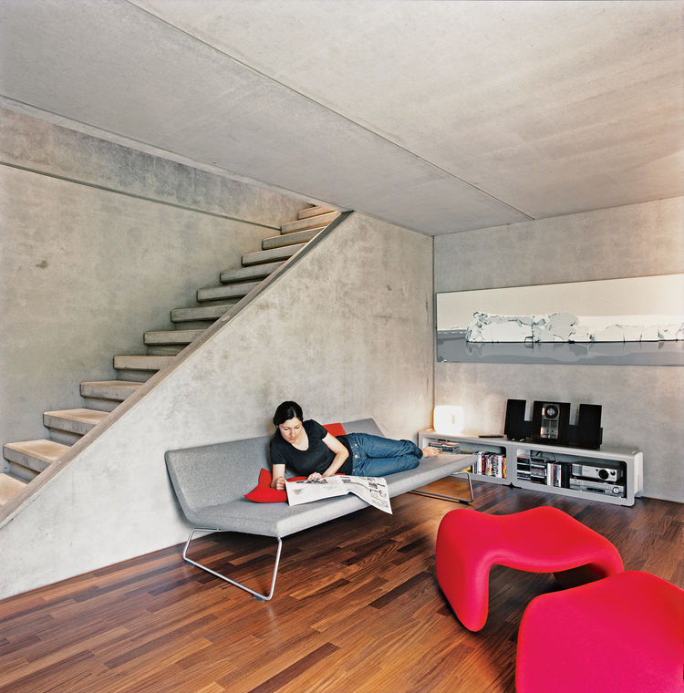 At the bottom of the stairs is a second living space that includes a fireplace. The couple couldn't find a television that didn't clutter the cool minmalism so they prefer to use a projector to watch movies. The sofa was designed by Barber-Osgerby for Cap
