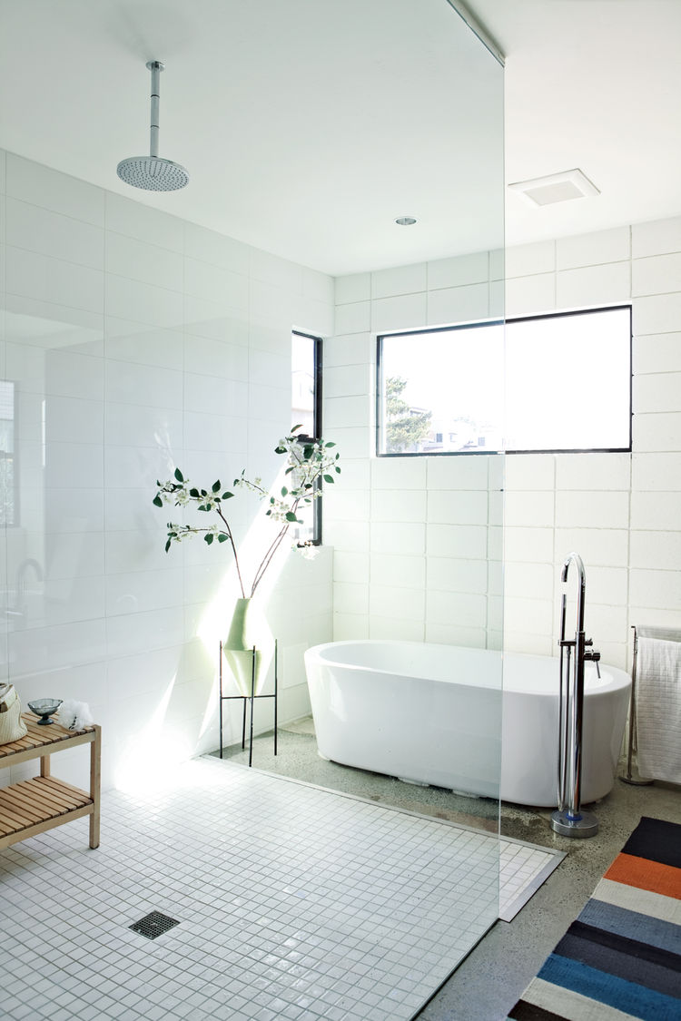 white bathtub, white tiled floor, multicolored striped bath mat