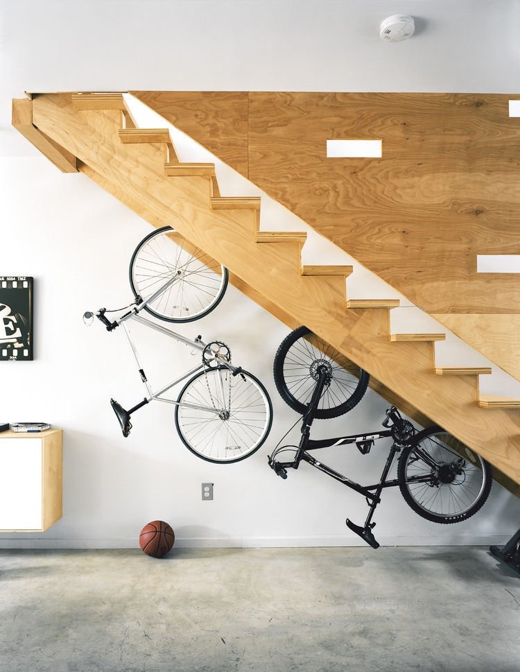 Plywood hanging bike rack by staircase