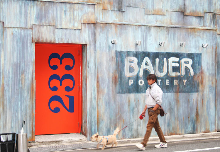 Corrugated metal facade and orange entry door at Bauer Pottery ceramics showroom in Tokyo