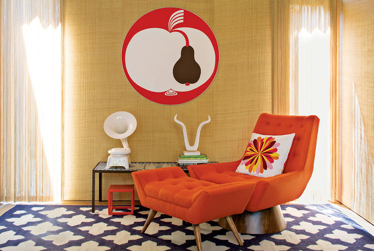 a red and white vintage print of an apple sits on a tan wall behind a red chaise lounge and ottoman with white art pieces sitting on a coffee table of black metal and glass