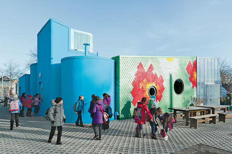 the blue exterior of a Brooklyn school with a learning garden
