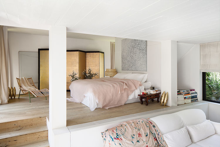 a white walled bedroom with a white bed and a rose colored throw in from of a Japanese screen and a teak chair