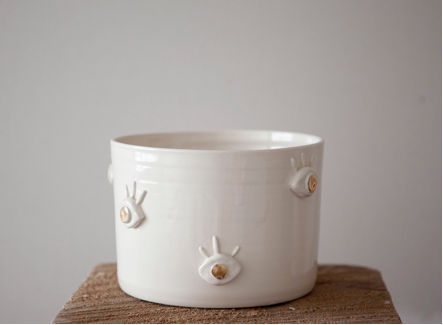 a ceramic planter with gilded eye designs