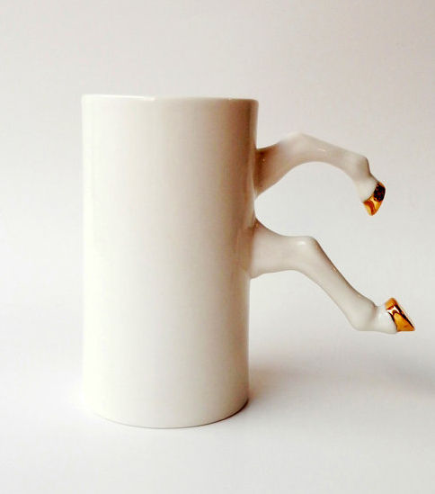 a white ceramic mug with gold-tipped horses' hooves acting as a handle