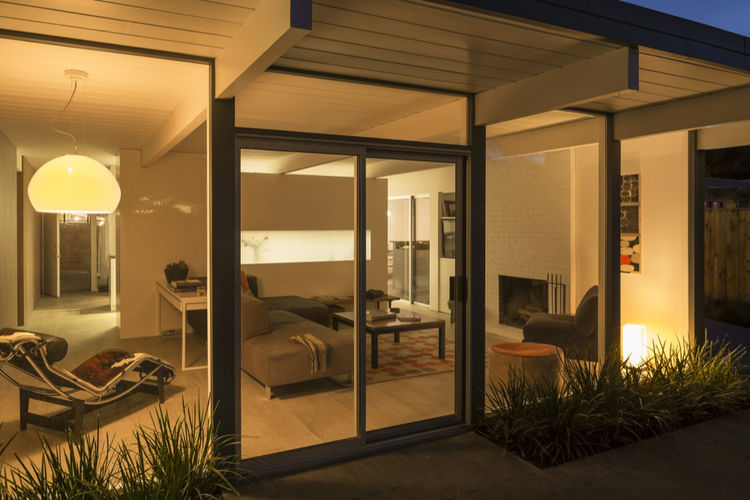 the renovated exterior of an Eichler home's living room by night