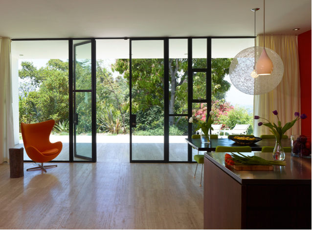 the view of the garden through the windows of the open-concept kitchen and dining spaces