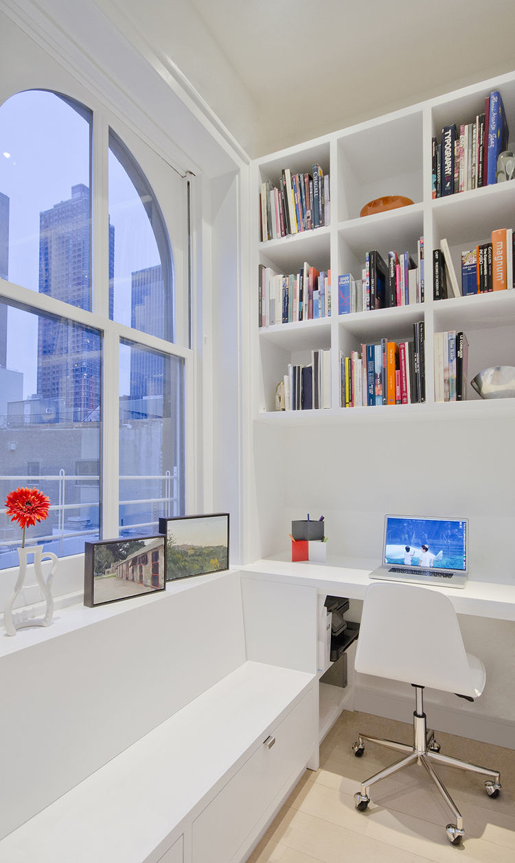 modern office with built-in shelving and white task chair