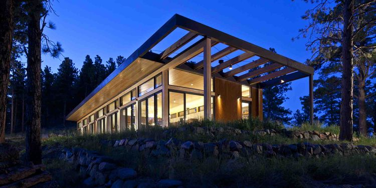 Exterior of modern wood home in the woods at night