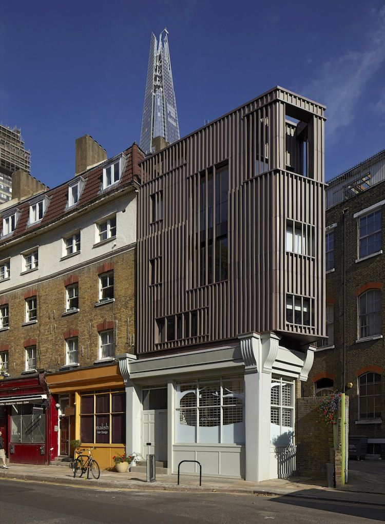 Triangular building in London with a wood-frame addition