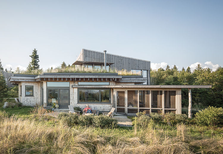 Wooden home with a green roof in Maine
