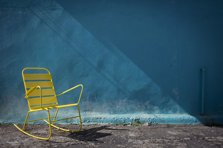 Banda yellow steel rocking chair against a blue wall.