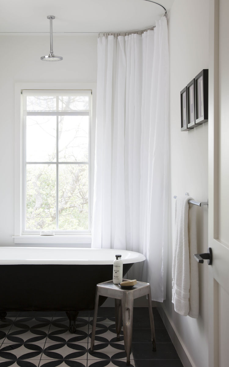 Guest bathroom with a black tub and black and white tiles