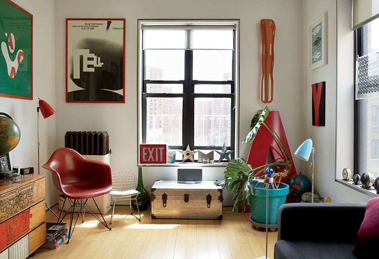 Bright modern living room renovation with red Eames chair and graphic prints