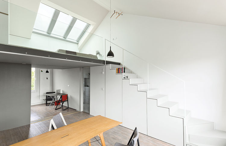 Modern white cabinets under the stairs with skylight above