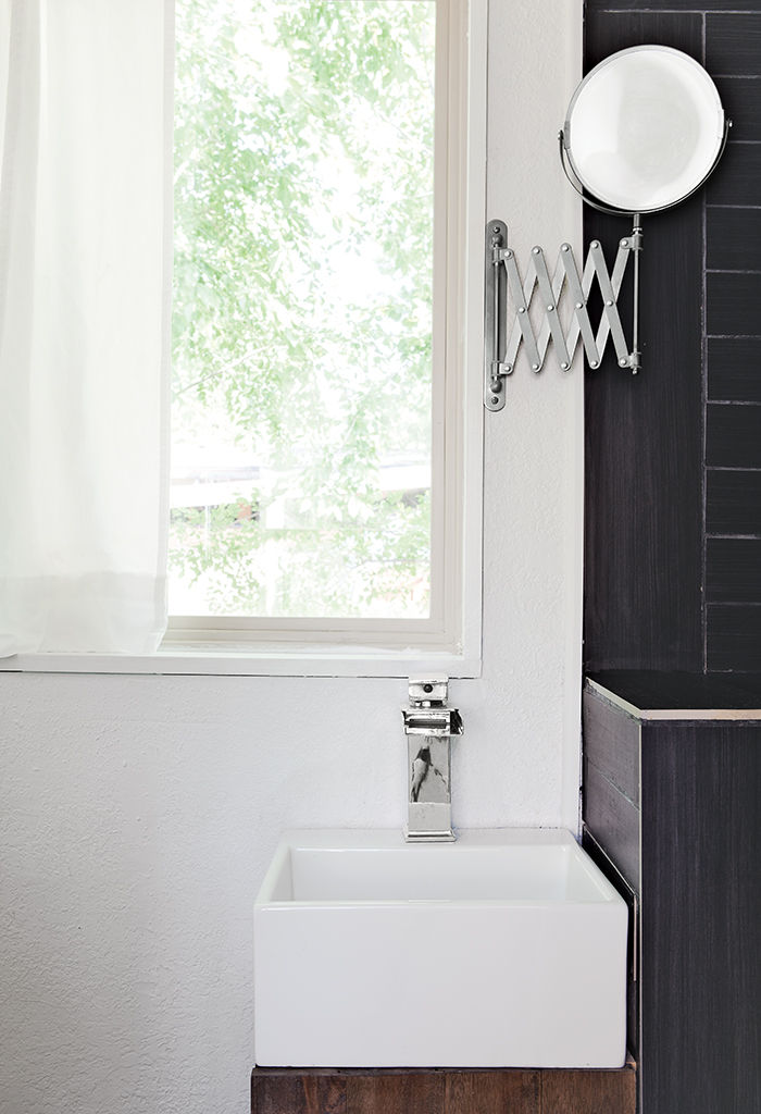 Minimal black and white bathroom with retractable mirror.