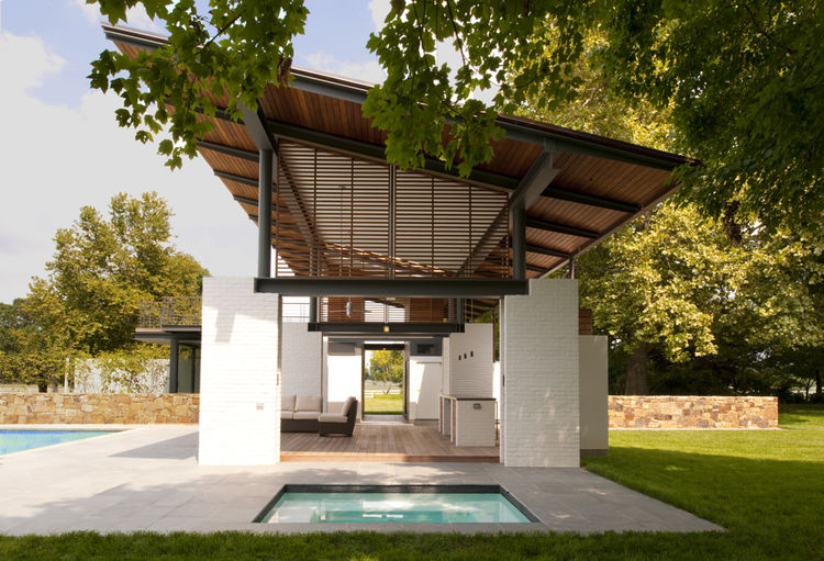 White brick piers suspending cantilevered roof by pool