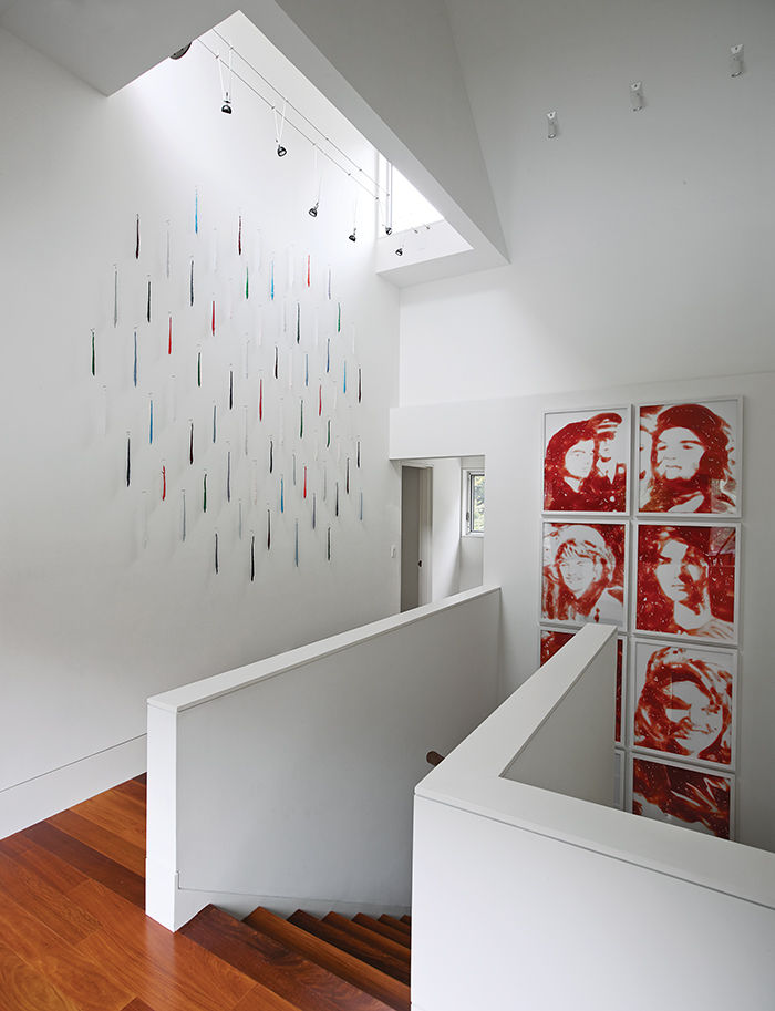 White stairwell with Jacqueline Kennedy artwork and skylight