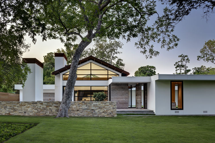 Renovated ranch home with limestone walls and gabled Cor-Ten roof
