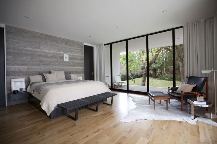 Modern Texas master bedroom with reclaimed wood wall and Finn Juhl chair