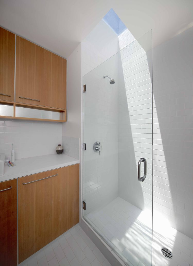 Modern bathroom with skylight and glass door