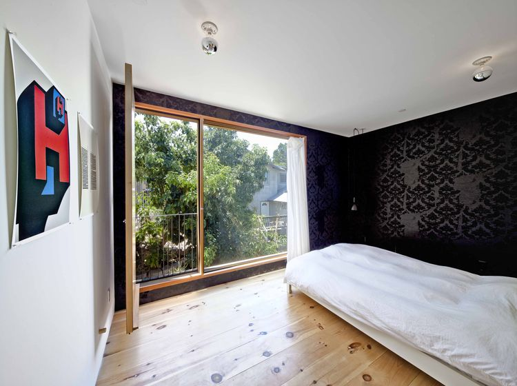 Wood floor bedroom with black wallpaper and balcony.