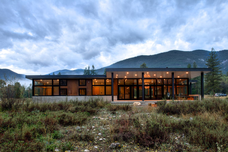 Exterior of Washington mountain home with floor-to-ceiling windows and concrete skirt.