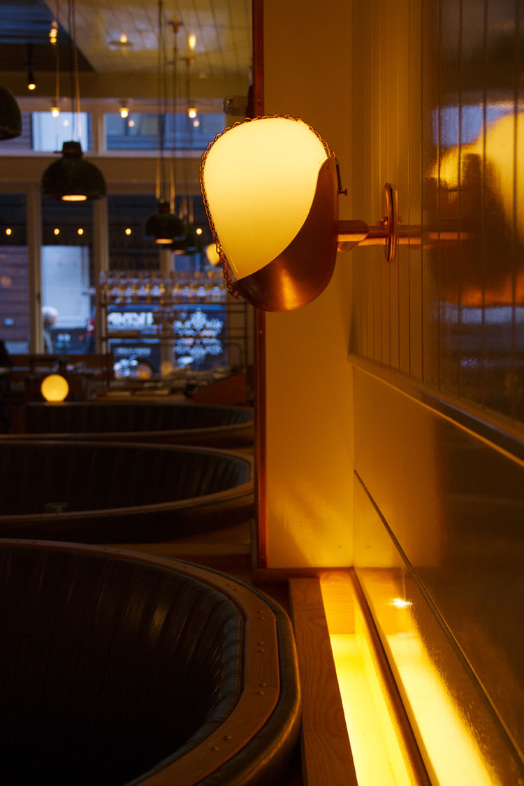 Roman and Williams New York City restaurant design with glass and copper wall sconces
