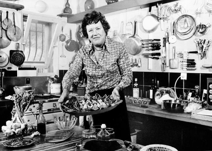 Julia Child in her kitchen with a pegboard wall
