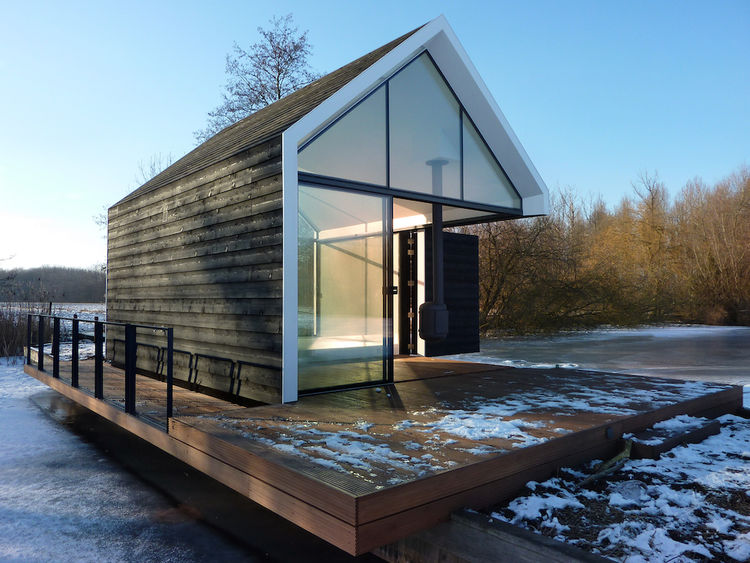 Prefab cabin with glass walls and folding wood door