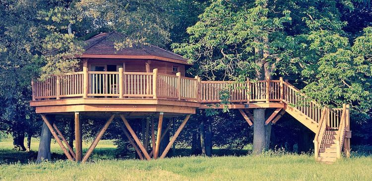 Bower House Construction tree house with wood staircase and railing