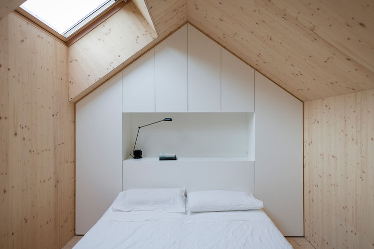 Pitched roof bedroom with skylight and wood walls