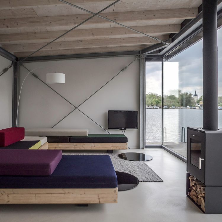 House boat in Berlin with colorful sofas and wood-burning stove